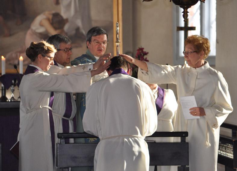 Kädet laskettu papin päälle alttarilla virkaanasettamisessa.