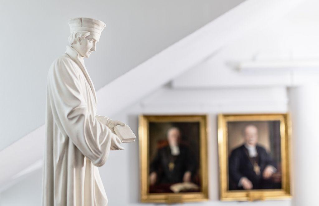 Mikael Agrikolan valkoinen patsas, takana seinällä kahden piispan muotokuvat.