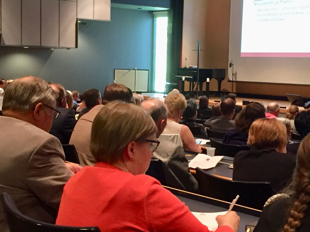 Osallistuvia henkilöitä auditoriossa.