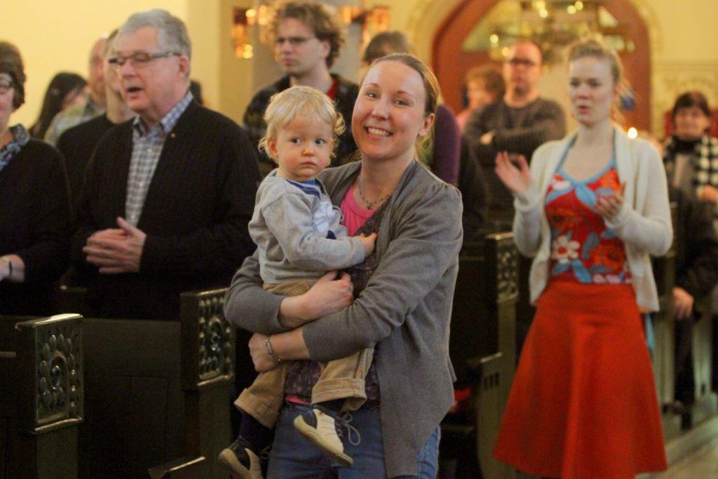 Hymyilevä äiti lapsi sylissä kirkossa