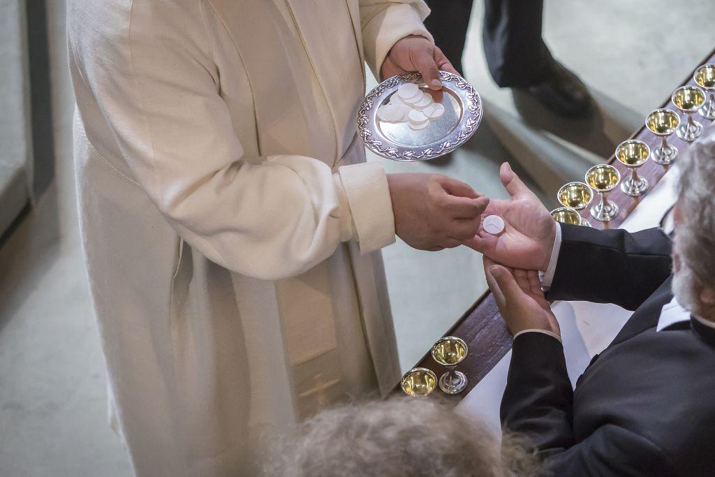 Pappi ojentaa ehtoollisleipää seurakuntalaiselle.