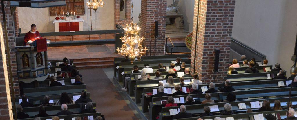 Kirkkoherra saarnaa kirkossa jossa paljon kuulijoita