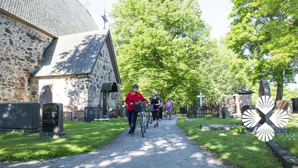 Pyhiinvaeltajia pyöriensä kanssa kirkon vieressä