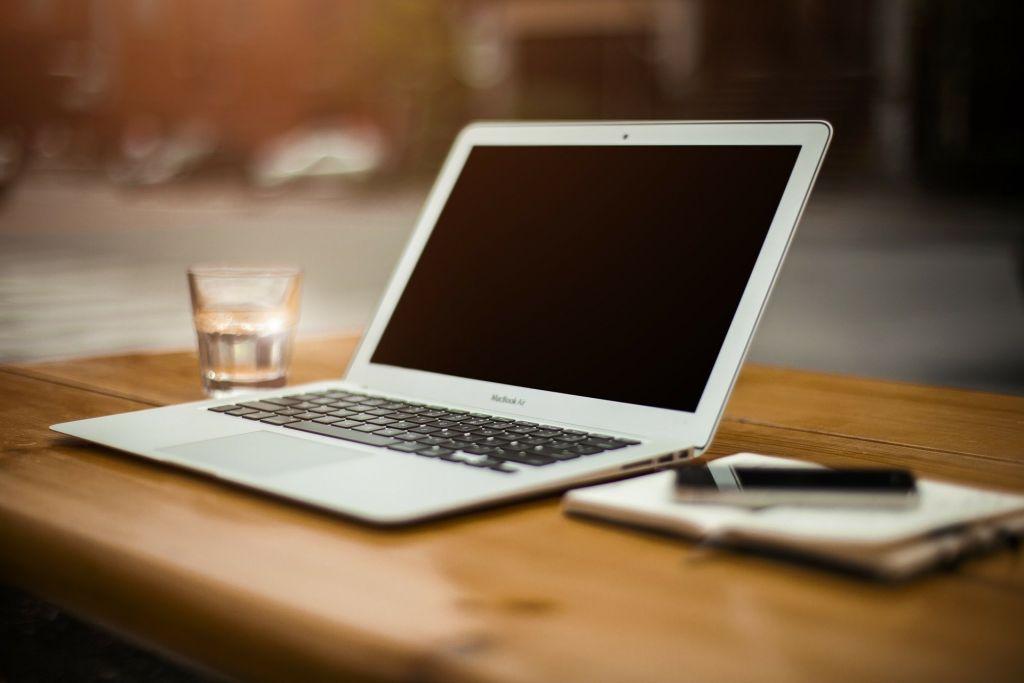 Kannettava tietokone pöydälla muistiinpanovälineiden kera.